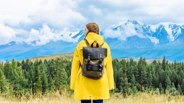 Hicker donna con zaino guardando le montagne. concetto di viaggio e avventura.