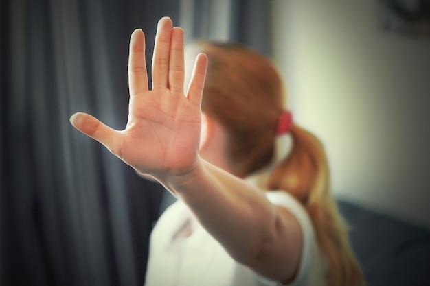La donna nasconde il suo viso a portata di mano. donna che tiene la mano tesa verso la telecamera, coprendosi il viso, evitando di essere vista o fermando un problema