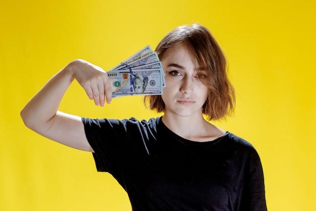 Donna che si nasconde dietro un mucchio di banconote e festeggia su sfondo giallo.