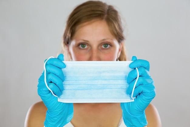 Donna che nasconde il viso dietro la mascherina chirurgica davanti a lei