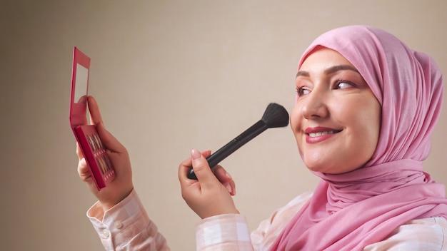 Donna in hijab che applica il trucco con un pennello mentre si guarda allo specchio.