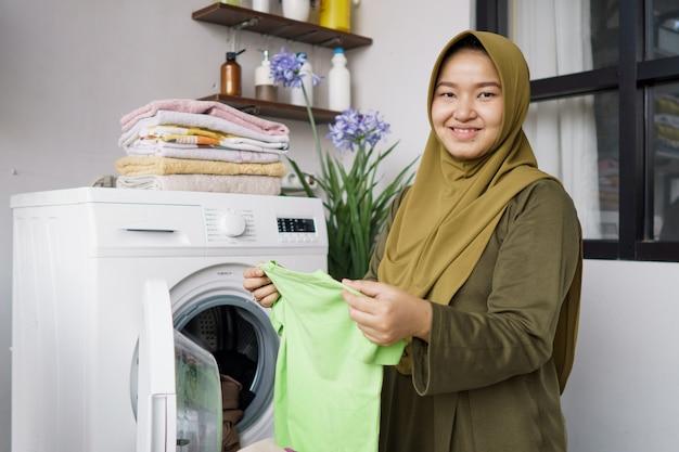 Donna in hijab che fa il bucato dei vestiti a casa usando la lavatrice