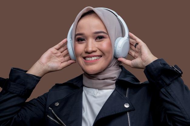 Donna in hijab in posa indossando cuffie wireless con un sorriso
