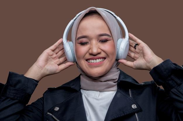 Donna in hijab in posa indossando cuffie wireless con sorridente mentre chiude gli occhi