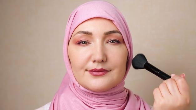 La donna in hijab accarezza il viso con una spazzola morbida mentre sorride alla telecamera.