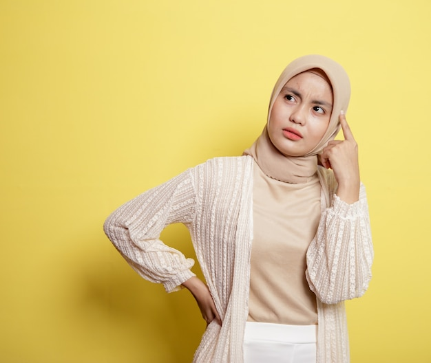 Hijab donna con un'espressione felice pensando a qualcosa di isolato su sfondo giallo