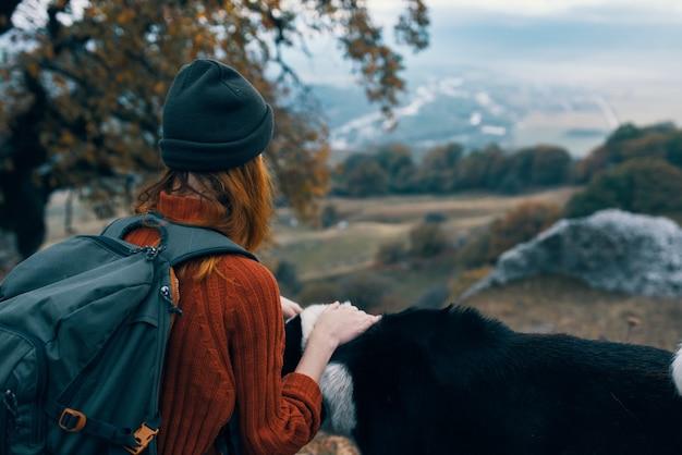 Viandante della donna accanto al viaggio di montagne della natura del cane