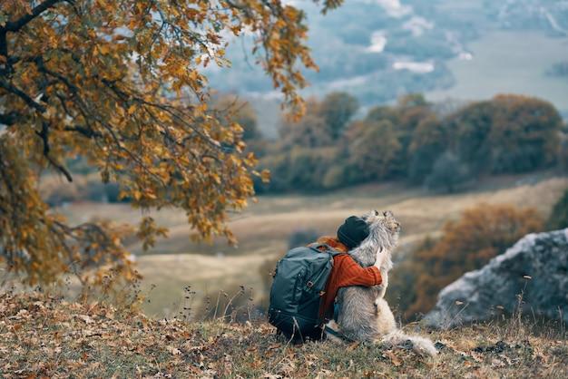 Viandante della donna che abbraccia con il cane sulla natura in montagna viaggia amicizia