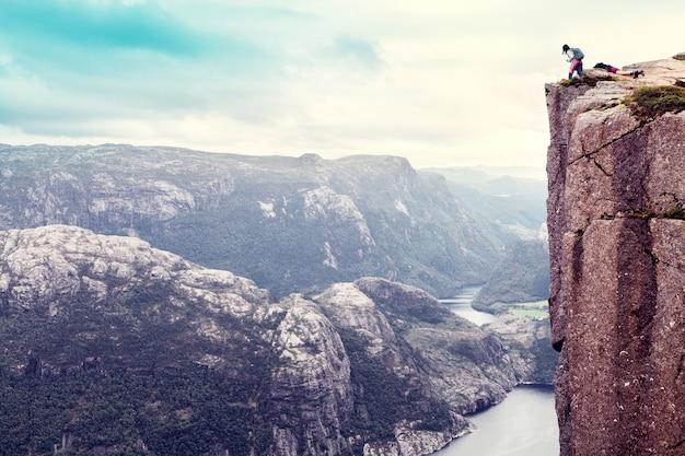 Escursionista donna che guarda verso il basso si erge sulla famosa roccia del pulpito preikestolen sul lysefjord