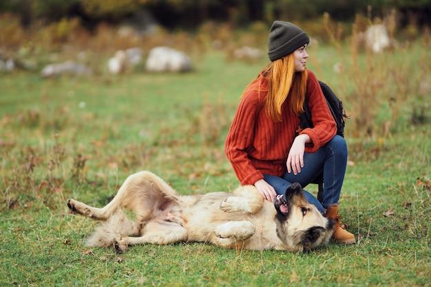 La donna escursionista in montagna si trova sull'erba accanto al cane che gioca a divertirsi