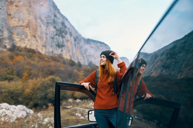 Viandante della donna in montagne vicino alla vacanza di paesaggio di viaggio in auto