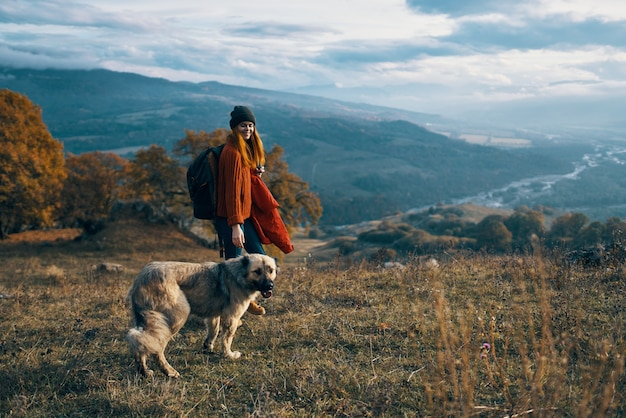 Le montagne della natura della viandante della donna viaggiano accanto all'amicizia di libertà del cane