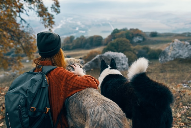 Escursionista donna in natura con cani viaggi avventurosi