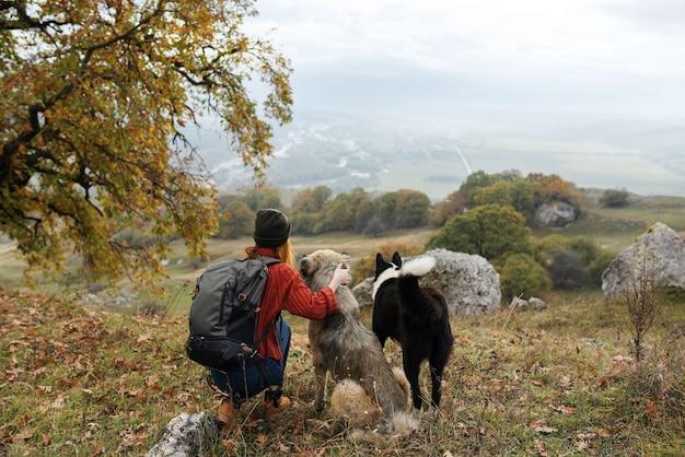 Viandante della donna in natura con le montagne del paesaggio di cani