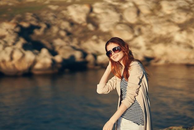 Viandante della donna all'aperto nelle montagne vicino al modello di vacanza del paesaggio di aria fresca del fiume