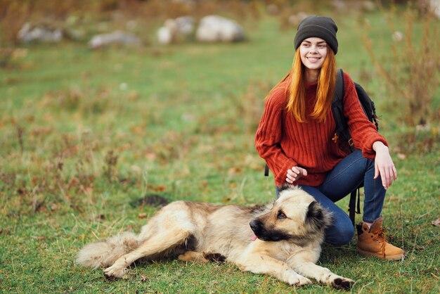 Viandante della donna che gioca con il cane nel viaggio di aria fresca della natura