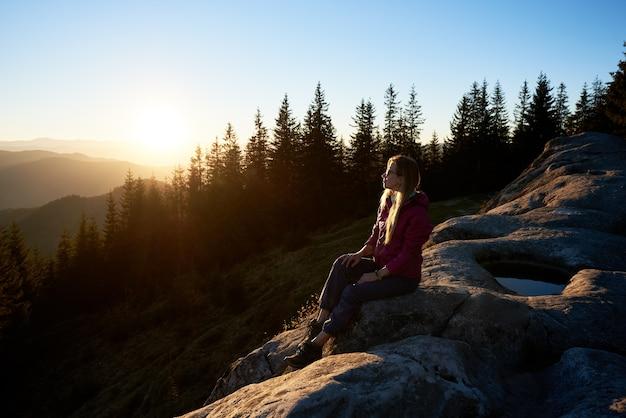 Viandante della donna che si siede sul masso in montagna al tramonto