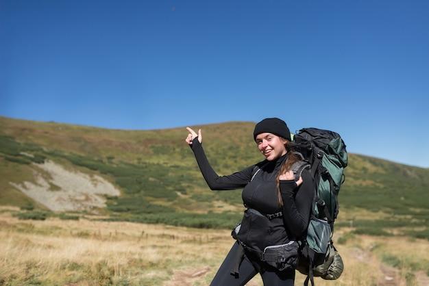 Escursionista donna si trova sulla cima della montagna, il dito indice della mano indica lo spazio vuoto