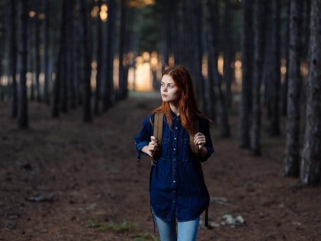 Escursionista donna a piedi nella foresta vicino a pini in natura. foto di alta qualità