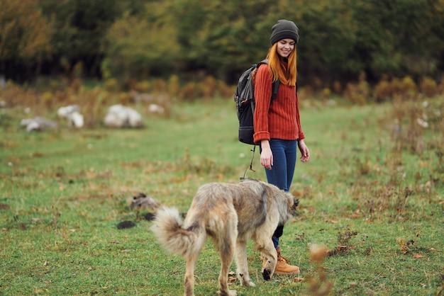 Viandante della donna che cammina il cane in natura nell'amicizia di viaggio della foresta