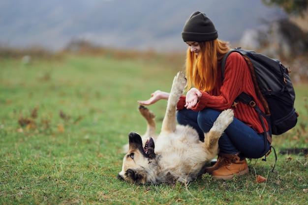La donna escursionista con uno zaino nel campo si gioca con un cane