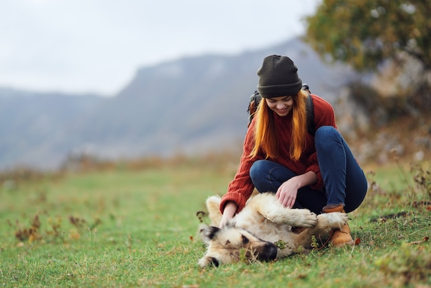 La donna escursionista con uno zaino sulla natura in montagna si gioca con un'amicizia canina