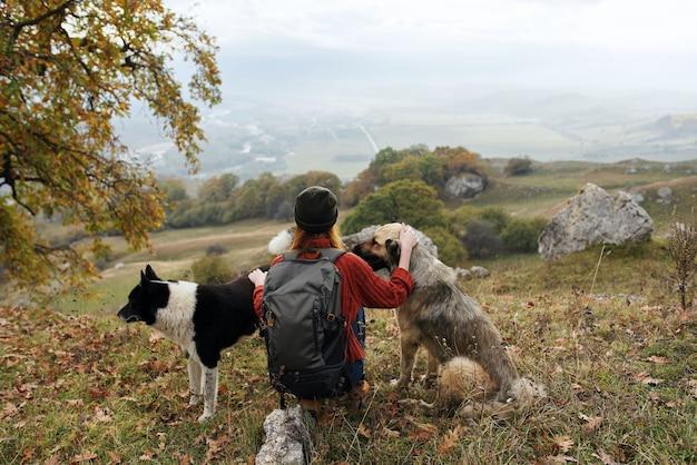 Viandante della donna con uno zaino in natura che accarezza un viaggio del cane