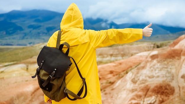 Viandante della donna con lo zaino sotto la pioggia in montagna in autunno. la ragazza con un impermeabile giallo mostra un segno di pollice in alto. concetto di viaggio e vacanza