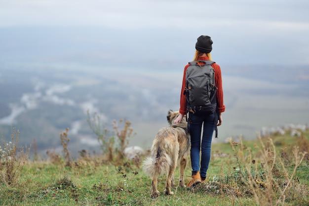 Viandante della donna con lo zaino con il cane nell'amicizia di viaggio delle montagne