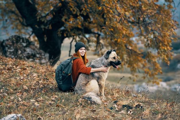 Viandante della donna con il cane in montagna ammira i viaggi nella natura