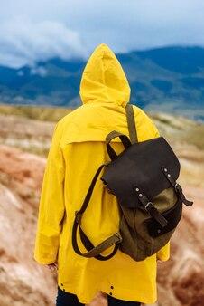 Viandante della donna in un impermeabile giallo con uno zaino sulle montagne con tempo nuvoloso