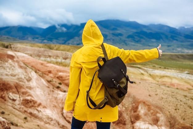 La viandante della donna in un impermeabile giallo con uno zaino mostra i pollici in su