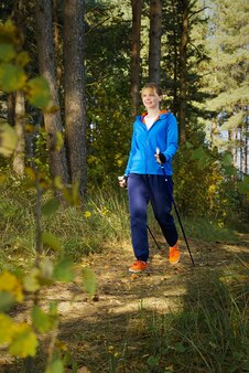 Donna che fa un'escursione lungo la strada forestale nella giornata di sole