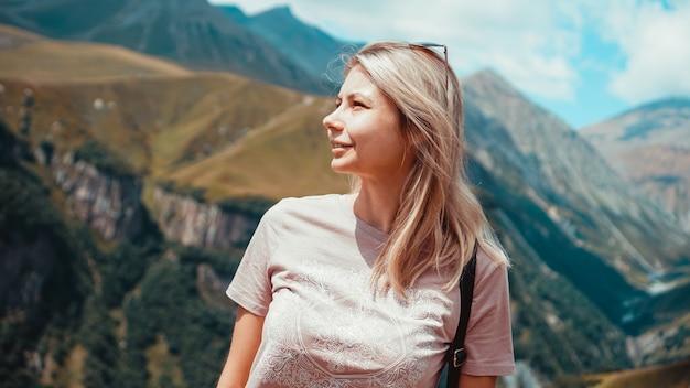 Donna che fa un'escursione in montagna durante la giornata di sole. vista di kazbegi, georgia
