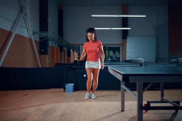 La donna colpisce una palla, tennis da tavolo allenamento in palestra