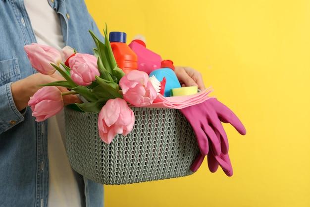 Cestino della stretta della donna con gli strumenti di pulizia su colore giallo