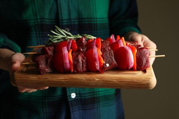 Bordo della stretta della donna con kebab di shish crudo, fine in su