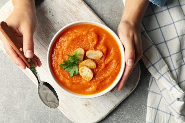 Donna tenere ciotola di zuppa di zucca, vista dall'alto
