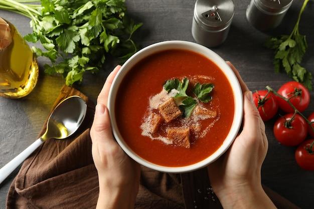 Donna tenere ciotola di gustosa zuppa di pomodoro, vista dall'alto