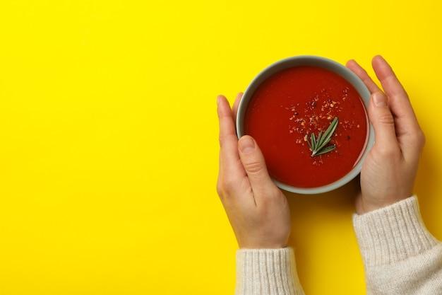 Ciotola della stretta della donna di zuppa di pomodoro saporita su colore giallo