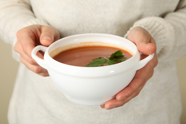 Ciotola della stretta della donna di zuppa di pomodoro saporita