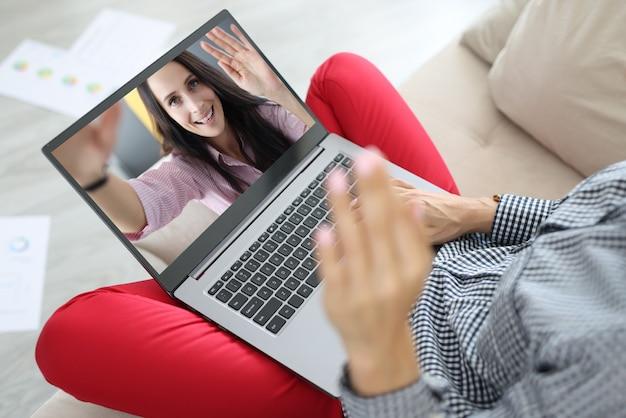 La donna tiene il computer in grembo e saluta. sulla donna allegra dello schermo del computer portatile