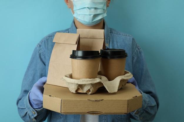 Contenitori di consegna della stretta della donna per cibo da asporto sull'azzurro