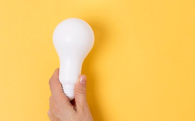 La donna tiene in mano la lampada eco. lampada led, tecnologie green. lampada ecologica. concetto di efficienza energetica.