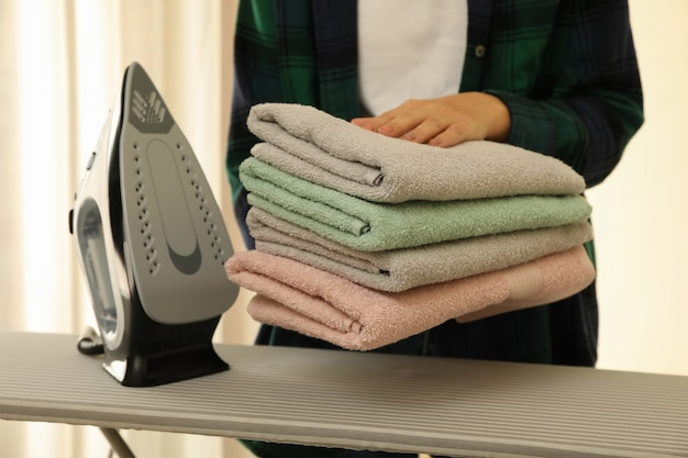Donna tenere mucchio di asciugamani su asse da stiro con ferro