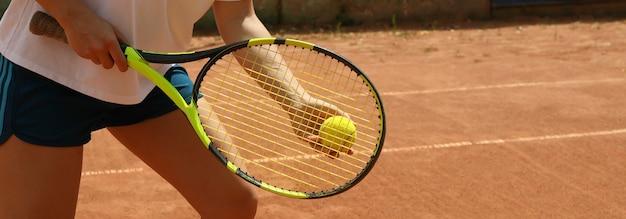 Donna tenere racchetta e palla da tennis sul campo in terra battuta