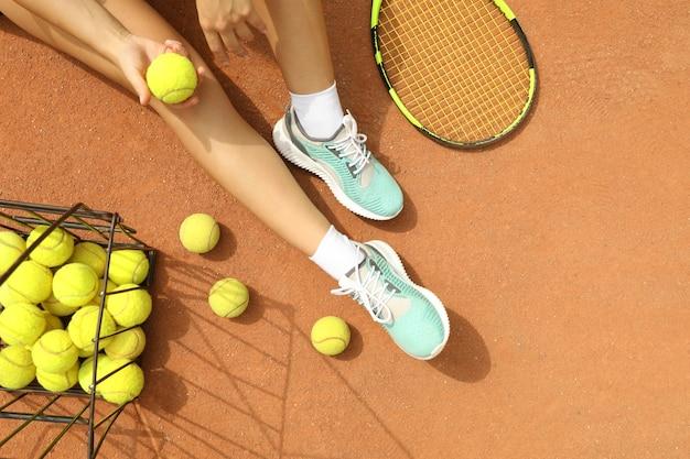 Donna tenere palla da tennis sul campo in terra battuta con racchetta e palline
