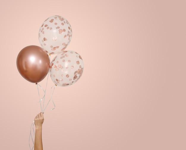 La donna tiene tre palloncini trasparenti e rosa isolati su beige con spazio per la cartolina d'auguri del testo
