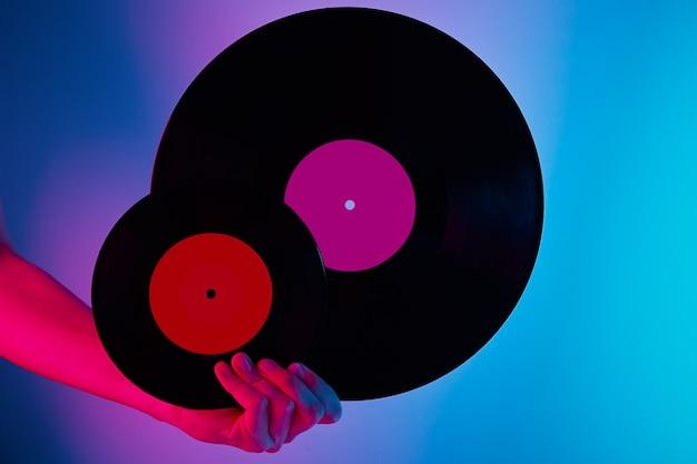 La donna tiene due dischi in vinile retrò nelle mani foto tonica