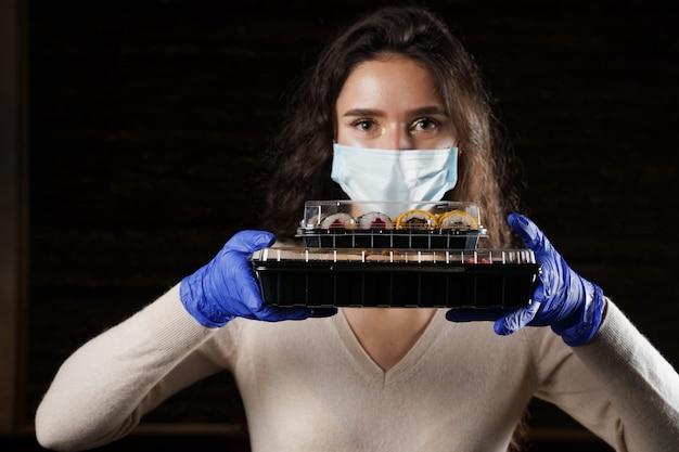 Donna che tiene in mano 2 scatole di sushi con guanti e maschera facciale